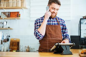Handsome smiling barista with beard taking order on cell phone and using tablet in cafeteria.jpeg